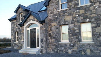 House and garage built with natural stone | Cut granite archway